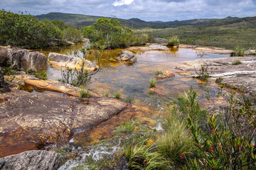 Rocky shallow riverbed above a waterfall with blooming scrubs and view, Biribiri State Park, Minas Gerais, Brazil