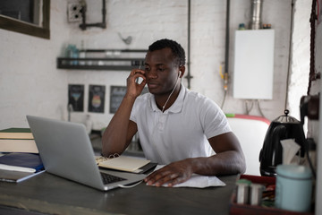 Diligent black student listening to online tutor