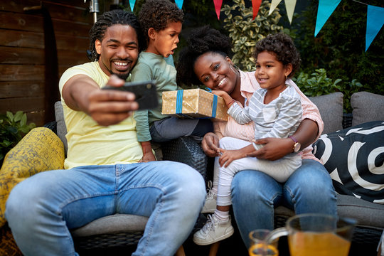 young african family gathered at birthday party taking selfie. togetherness concept