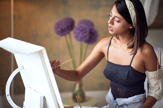 young adult female caucasian passionately painting. art, passion concept
