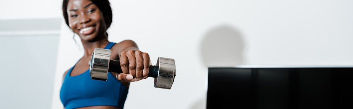 Horizontal image of african american sportswoman holding dumbbell with outstretched hand and smiling in living room