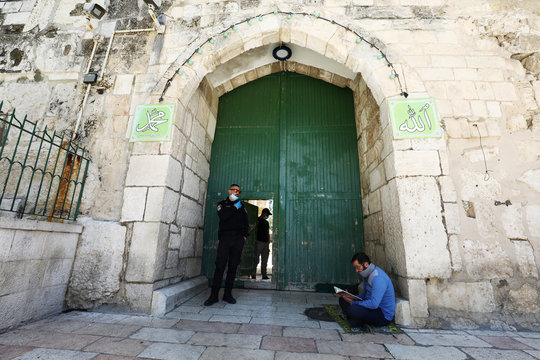 A Muslim worshipper reads the Koran at the entrance to the compound known to Muslims as al-Haram al-Sharif and to Jews as Temple Mount hosting Al-Aqsa mosque Jerusalem's Old City, amid coronavirus disease (COVID-19) restrictions