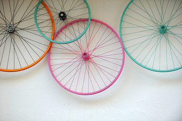 Poster Bicycle Old bicycle wheels colorful on the wall of a rental and repair shop, hipster decorative trend concept