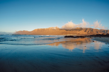Foto op Aluminium Canarische Eilanden Famara beach with reflection and mountains at sunset in Lanzarote at Canary islands