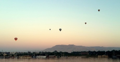 Poster Montgolfière / Dirigeable Hot Air Balloons Flying Over River Against Sky At Sunset