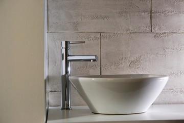Dettaglio di rubinetto moderno su lavabo elegante dentro un bagno.