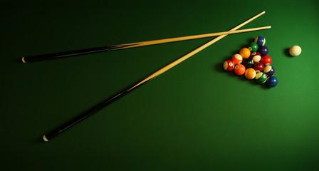 billiard cues and pyramid of multicolored pool balls on green billiard table