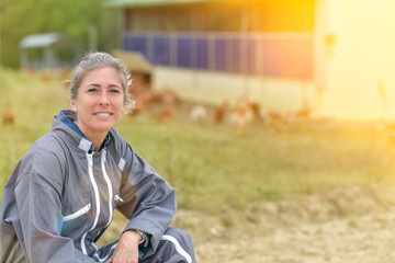 Portrait of a female farmer standing in the middle of her chicken breeding