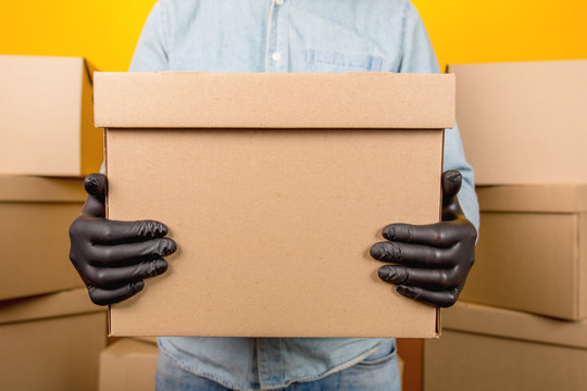 Close up of a delivery man in black latex gloves holding a cardboard box with a parcel on a yellow background