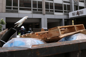 A worker loads a trash bin at the Liaison Hotel as it is renovated into a new Yotel property during the coronavirus disease (COVID-19) outbreak, in Washington