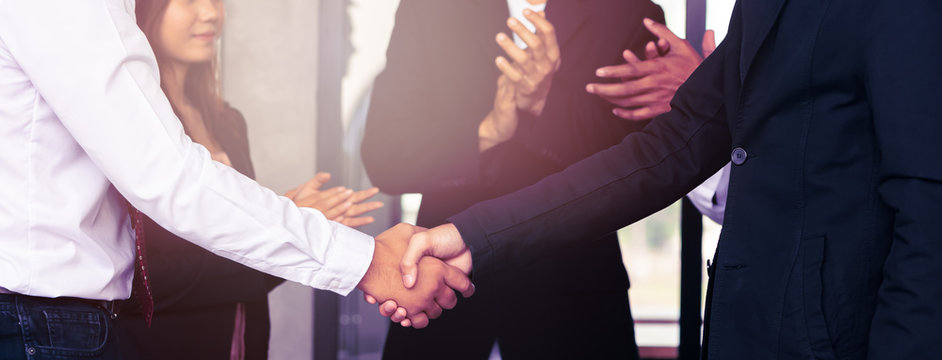 Businessperson handshaking together and colleagues applaud congratulating coworker with promotion in the meeting.