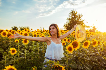 Tuinposter Zonnebloem Happy free woman opened arms walking in blooming sunflower field holding straw hat. Summer vacation
