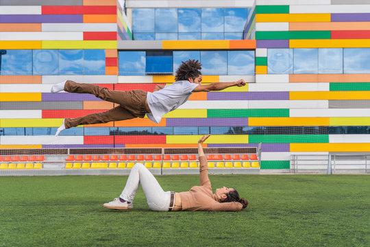 Dancer jumping super hero style over partner, lying on grass
