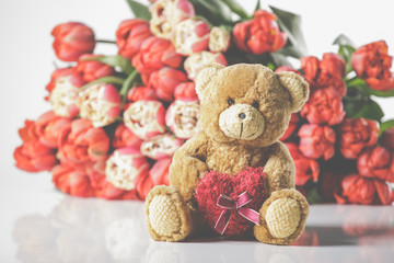 A large tulip bouquet, many flowers with red blossoms. With teddy bear.