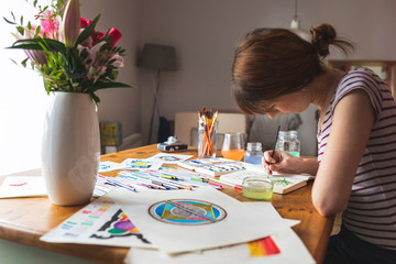 Woman sitting at desk painting with watercolours