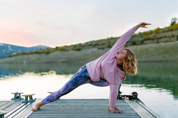 Young woman doing yoga on a jetty, triangle pose