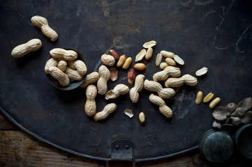Peanuts lying on rustic baking sheet