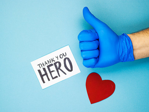 a hand with a raised thumb in a medical glove, a red heart and the inscription thank you to the heroes. gratitude to medical workers. support for doctors and nurses