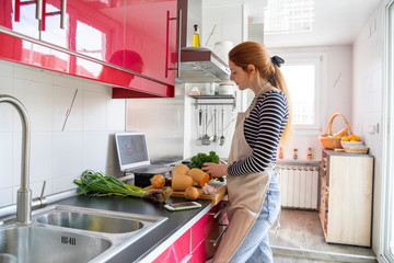 Young woman havig a video chat, while cooking a healthy meal