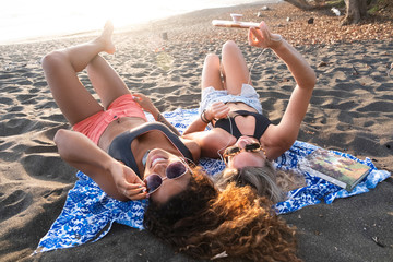Two happy women lying on the beach listening music on the phone, Costa Rica