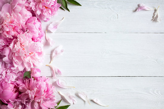 Wooden white background with pink peonies