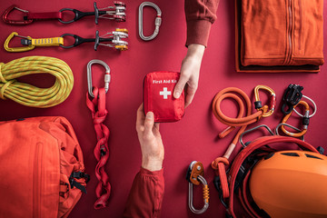Overhead view of woman handing over first aid kit to man with climbing equipment in background