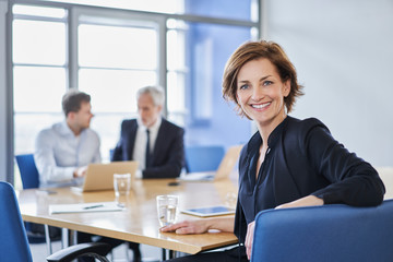 Portrait of smiling businesswoman during a meeting in office