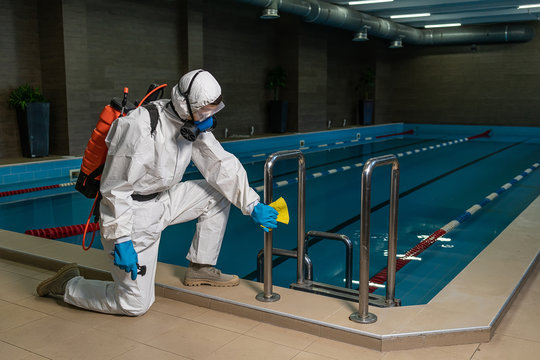 Cleaning and Disinfection in pool amid the coronavirus epidemic Gym cleaning and disinfection Infection prevention and control of epidemic. Protective suit and mask and spray bag COVID-19