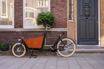 Foto op Plexiglas Fiets Typical dutch carrier bicycle parked in front of a house. Modern urban parents use these carrier bikes to transport their children or groceries