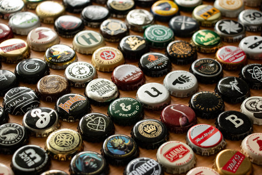 A variety of international beer bottle caps arranged in rows on a wood table.