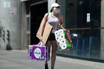 A woman carries toilet paper down the street on the first day of the reopening of some businesses in Los Angeles, as the global outbreak of the coronavirus disease (COVID-19) continues, in Los Angeles