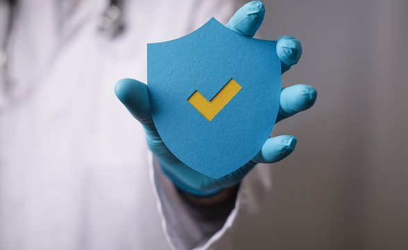 Papercut of a safety shield with a yellow checkmark in the hands of a doctor