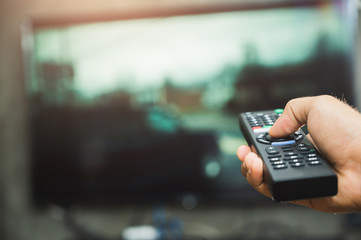 Young man holding television remote control. Hands pointing to tv screen set and turning it on or off select channel watching tv on his sofa at home in the living room relax..