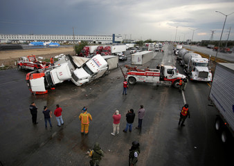 People stand near damaged trucks after a tornado hit the municipality of Apocada state of Nuevo Leon