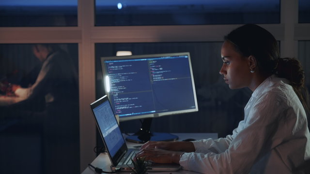 Side view of african american female engineer working on computer in electronics laboratory. Doing Development of Software and Hardware. She wearing a lab coat