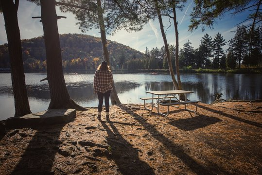 Rear View Of Woman Standing By Lake At Allegany State Park