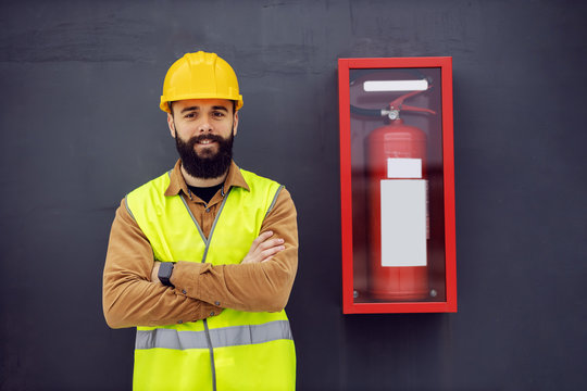 Young smiling cheerful attractive bearded worker in vest, with helmet on head standing next to fire fire extinguisher with arms crossed. Safety comes first.