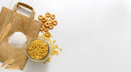 Products made of wheat flour. White flour, wheat ears and raw pasta in bowl on paper package and white background top view copy space
