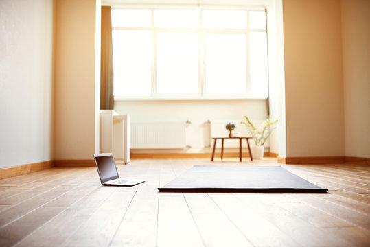 yoga room with big light window in modern flat. Yoga mat and computer on the floor, no people
