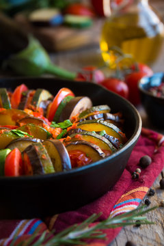 Homemade ratatouille made with sliced vegetables: zucchini, tomatoes and eggplant. Delicious vegan dish