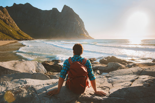 Man sitting on Kvalvika beach enjoying ocean view travel vacations eco tourism outdoor backpacking in Norway healthy lifestyle summer trip