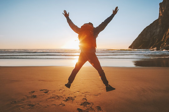 Man jumping on beach travel healthy lifestyle active vacations outdoor adventure success happy emotions traveler enjoying sunset ocean landscape