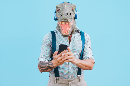 Senior tattooed man with t-rex mask using smart mobile phone while listening music during Coronavirus time - Crazy man wearing funny party mask for Covid-19 prevention - Focus on face