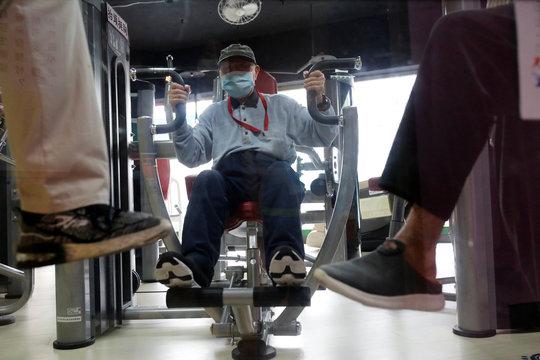 Seniors exercise on gym equipment at elderly day care center in Taipei