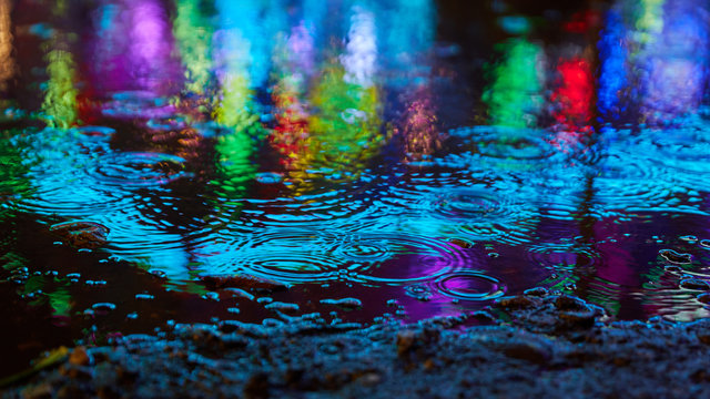 Blue reflections in the water when it rains at a fun fair