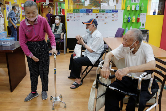 Seniors wait to go home after a day at an elderly day care center in Taipei