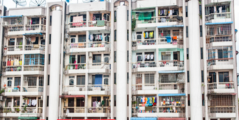 Typical Asian apartment block comprising series rooms with exterior balconies all with laundry hanging out to dry.