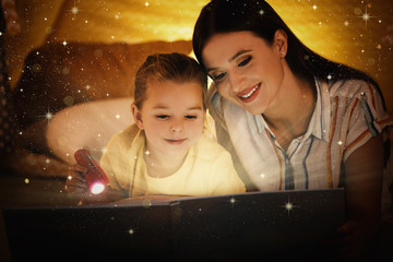 Mother with little child reading magic book at home