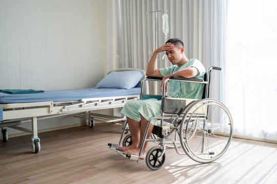 patients man is suffering from a headache pressing fingers to temples, closing eyes to relieve pain with helpless face expression sit on wheelchair