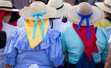 Deurstickers Canarische Eilanden Back of anonymous women in traditional costumes at local festival in Gran Canaria, Spain. Popular celebration with people on wicker hats and colorful scarfs in Las Palmas city, Canary Islands